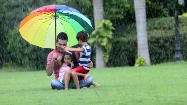 Adult man enjoying in the rain with his kids, Delhi, India