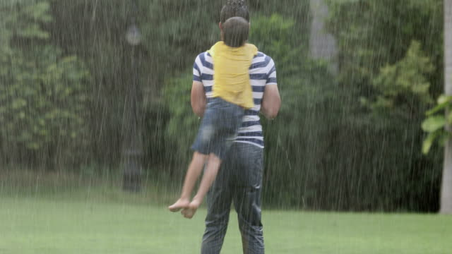 Adult man enjoying in the rain with his son, Delhi, India