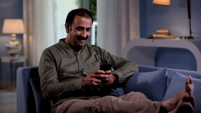 Adult man showing mobile phone at home, Delhi, India
