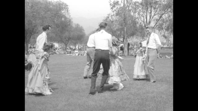 Adult men and elementaryage children stand in a square as they wait to begin an outdoor square dance performance VO music and dance calls dancers...