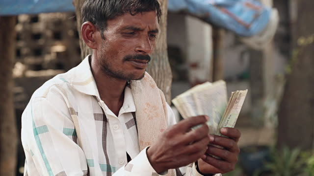 Adult men counting indian rupees, Haryana, India