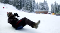 Adult people enjoying in children's winter game,tobogganing