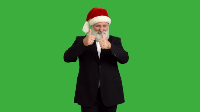 adult senior beard man dancing and calling to him  in a hat santa claus  on a green background