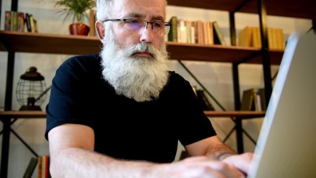 Adult senior bearded man working on laptop