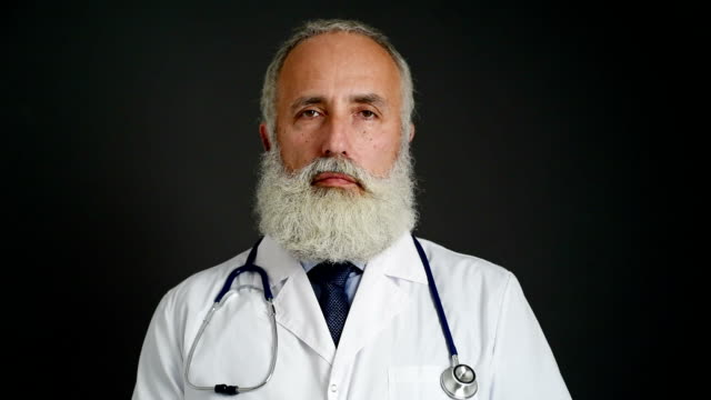 adult senior doctor  looking at the camera on a dark background