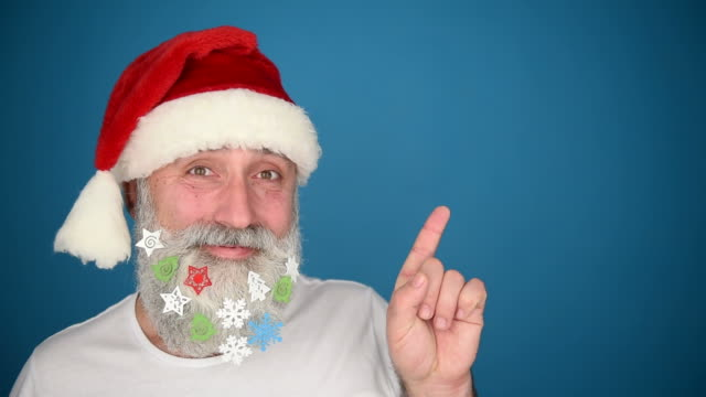 Adult senior man showing a copy space and showing the thumb in the Santa Claus hat on a blue background