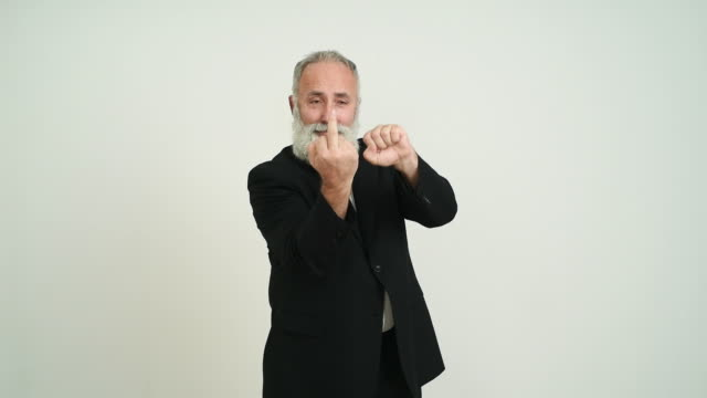 Adult senior man showing a middle finger  on a grey background