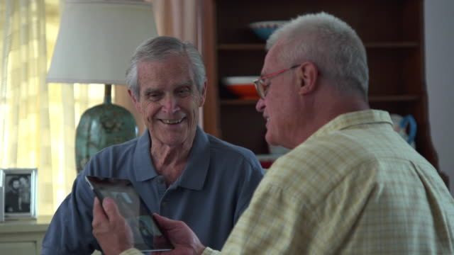 MS Adult Son Showing Video of Grandson to Senior Great Grandfather on Tablet Computer / Richmond, Virginia, United States