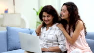 Adult woman chatting on laptop with her daughter, Delhi, India