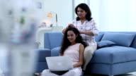 Adult woman combing her daughter hair, Delhi, India