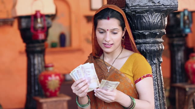 Adult woman counting indian rupees note, Delhi, India