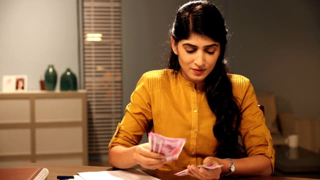 Adult woman counting indian two thousand banknotes at home, Delhi, India