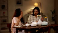 Adult woman eating dinner with her daughter, Delhi, India
