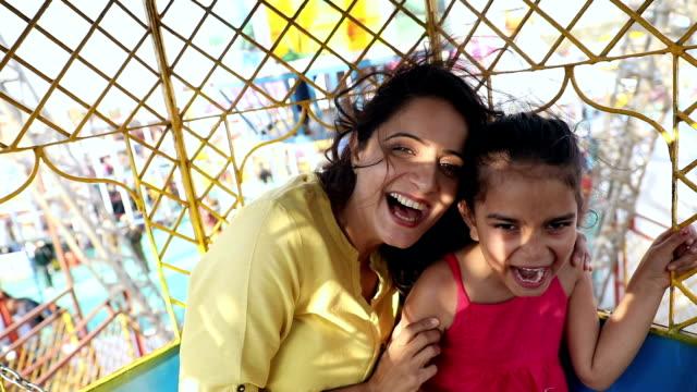 Adult woman enjoying ferris wheel with her daughter at suraj kund fair, Haryana, India