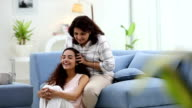 Adult woman massaging her daughter hair, Delhi, India