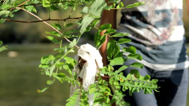 Volwassen vrouw oppakken van Plastic tas geplakt op rivieroever
