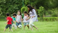 Adult woman playing football with kids in the park, Delhi, India