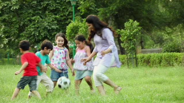 Adult Woman Playing Football With Kids In The Park Delhi ...