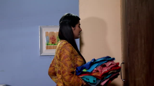 Adult woman putting clothes into cupboard, Delhi, India