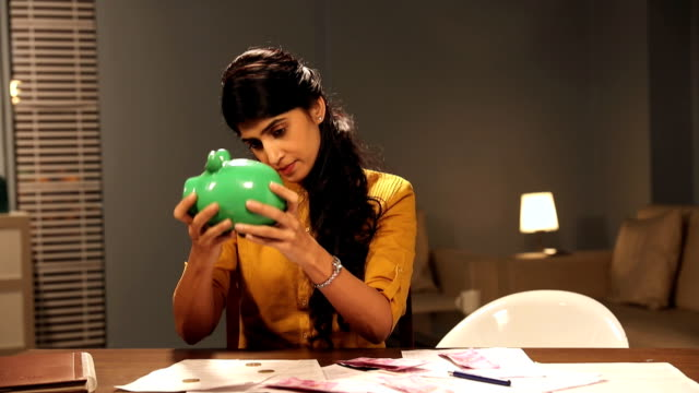 Adult woman shaking a piggybank, Delhi, India
