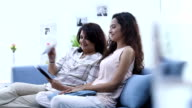 Adult woman showing pictures of groom to her daughter, Delhi, India