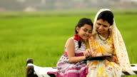 Adult woman teaching her daughter in the farm, Haryana, India