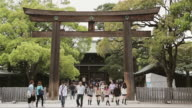 MS Adults and schoolgirls walk through a torii zt Meiji Shrine / Tokyo, Japan