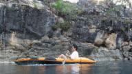 Adventurous Woman paddling a kayak close to a wild stone wall.