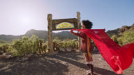 SLO MO. Adventurous young woman holds a flowing red scarf like a cape in the wind in a desert ghost town.