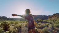 SLO MO. Adventurous young woman laughs and twirls in the desert sun.