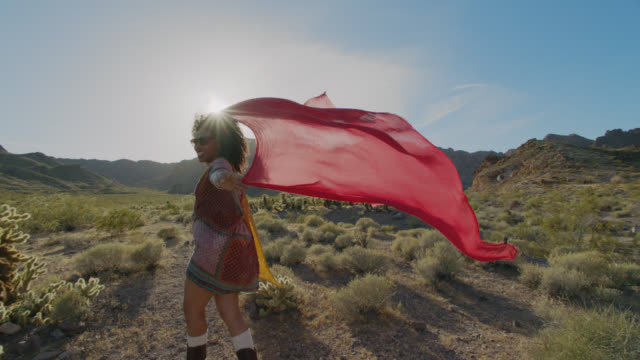 SLO MO. Adventurous young woman throws flowing red scarf overhead in the desert wind and smiles at camera.