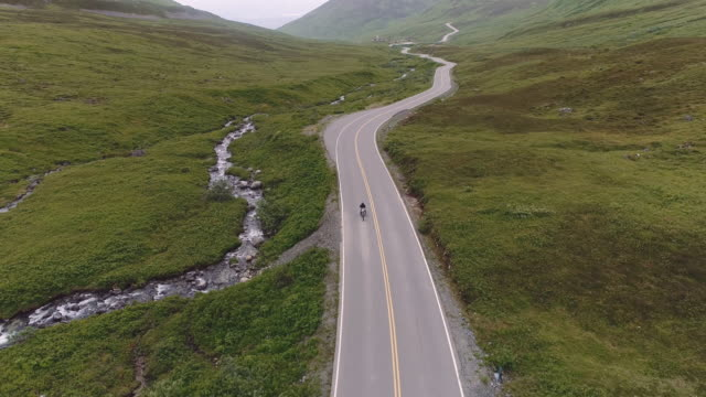 UHD 4K Aerial: Adult male on a motorcycle riding down a scenic highway