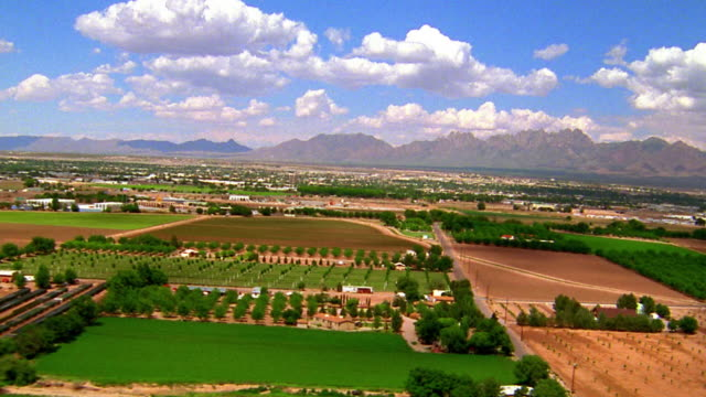 Aerial aircraft point of view over farmland, ranches, and river with mountains in background / El Paso, Texas