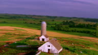 Aerial aircraft point of view over old farm buildings with silo / Iowa