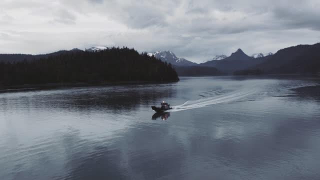 UHD 4K Aerial: Alaska fishing boat cruising at dusk along the coastline