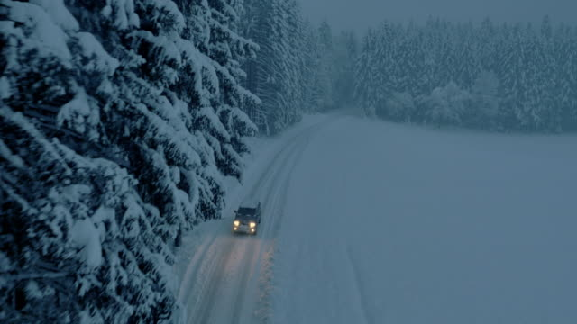 Aerial All terrain vehicle on snowbound forest road at night