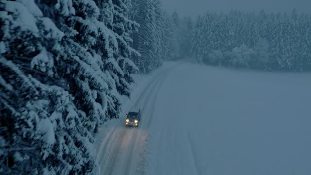Luchtfoto alle terrein voertuig op snowbound bos weg bij nacht