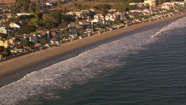Aerial TS WS along residential beachfront homes / Malibu, California, United States.