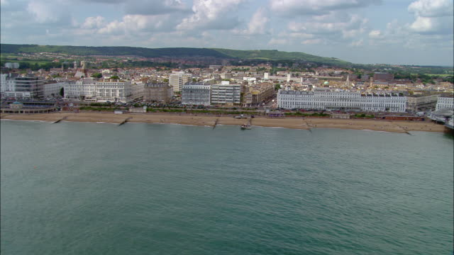 Aerial along the coast of Eastbourne / over Eastbourne Pier / East Sussex, England