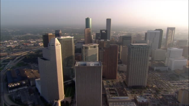 Aerial approaching downtown/ over skyscraper rooftops to traffic on motorway/ Houston, Texas