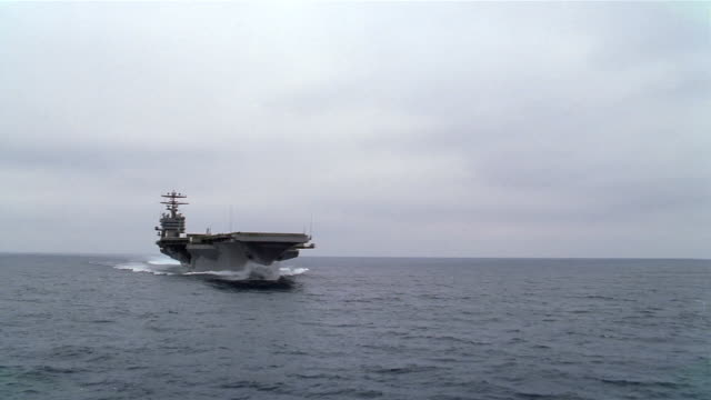 Aerial approaching USS Carl Vinson sailing through Pacific with F-14 Tomcat on deck / California