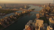 Aerial -At sunrise, a pivoting turn from mid-town Manhattan toward Roosevelt island, while looking south over the East River and Queensboro bridge, with the lower Manhattan skyline and Freedom Tower visible.
