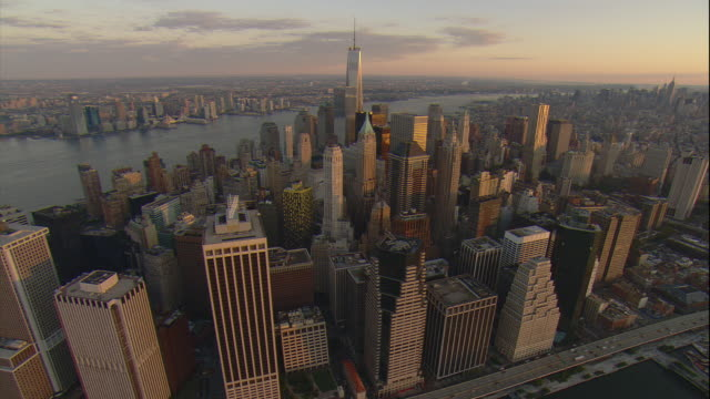 Aerial -At sunrise, flying from Governor's island up the East River while pivoting around the financial district of lower Manhattan including the Freedom Tower.