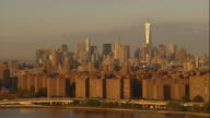 Aerial -At sunrise, from low over the East River, traffic on FDR drive in foreground with Stuyvesant Town and the lower Manhattan skyline and Freedom Tower behind.