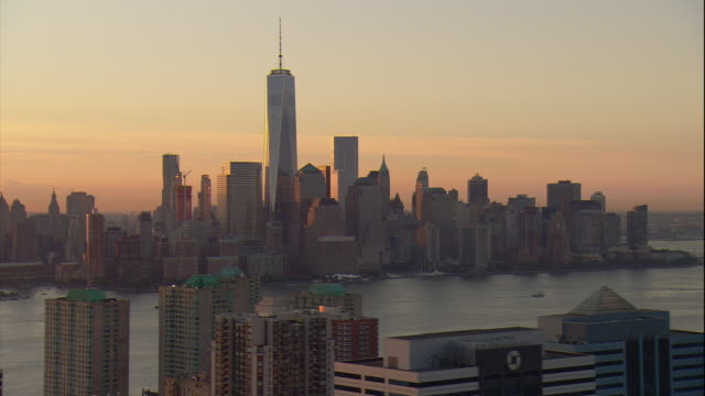 Aerial -At sunrise, looking over buildings in Jersey City, NJ at the lower Manhattan skyline including the Freedom Tower.