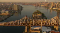 Aerial -At sunrise, traffic on the Queensboro bridge with a ZO and pan to reveal part of Roosevelt island, the East River, and Manhattan skyline, with the Freedom Tower visible.