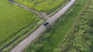 Aerial: Black SUV car driving along green fields