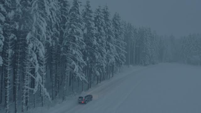 Luchtfoto auto rijden langs sneeuw bedekte bos weg bij nacht