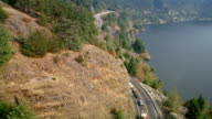 Aerial cars and trucks lined up in traffic jam on side of mountain overlooking sound / Canada