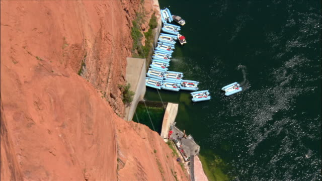 Aerial cars driving over Glen Canyon Bridge / tour boats on Colorado River / Page, Arizona